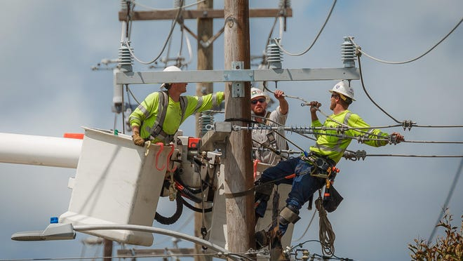 Lake Worth Electric Utility workers do maintenance on a power pole in the city on Tuesday, September 12, 2017. The city will start cutting off power to those who have not paid their bills on Friday, July 17, 2020.