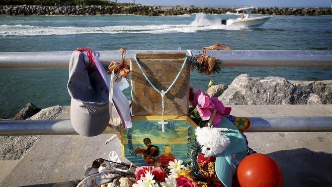 A weathered memorial of items for Austin Stephanos and Perry Cohen sits on the walkway at the Jupiter Inlet in 2016.