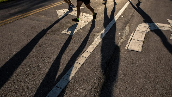 Shadows created by runners during the inaugural Race for the Red & Blue First Responders 5K Run/Walk Saturday, September 8, 2018 at the Wellington Amphitheater.