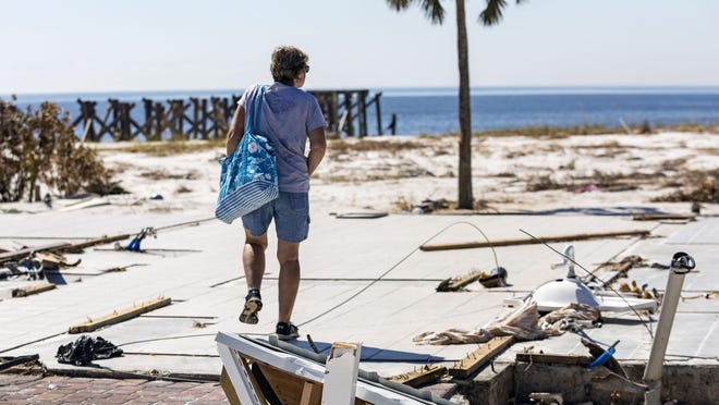 Caron Spencer, of Tallahassee, walks over the floor of her house, the only thing remaining, in Mexico Beach Tuesday, October 16, 2018, after Hurricane Michael hit north Florida. It was her first time back since the storm hit.