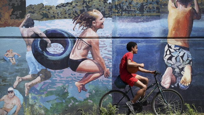 "A young cyclist passes the Mural Arts mural ""Afternoon by the Water"" along Aramingo Avenue in Philadelphia on Wednesday, July 29, 2020. The mural was created by artists James D. Burns, Charles Barbin, Anastasia Wong, and Karl Yoder. Temperatures in the Philadelphia region reached the 90s again Wednesday, according to the National Weather Service."