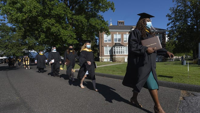 Geralda Saint Jean, right, front shown here walking across campus with classmates at the end of the graduation ceremony at Rowan University, Rowan University, Glassboro campus.