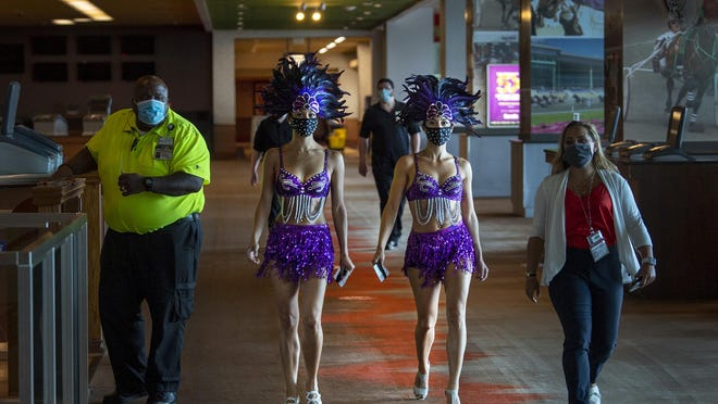 Casino staffers, dressed as showgirls, Angela Simpkins, left, and Vanessa Harkins, walk to the casino floor minutes before the reopening of Harrah's Philadelphia Casino and Racetrack in Chester on Friday.