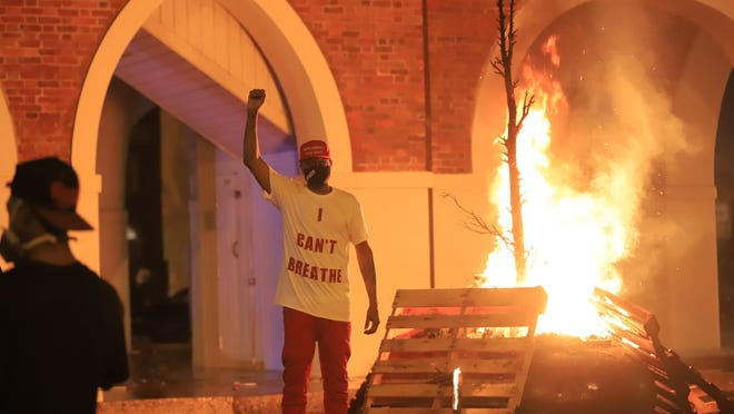 A protester stands near the Market House after it was lit on fire on May 30. A City Council committee that met this week will be recommending the fate of the building but it will be its last topic of discussion.