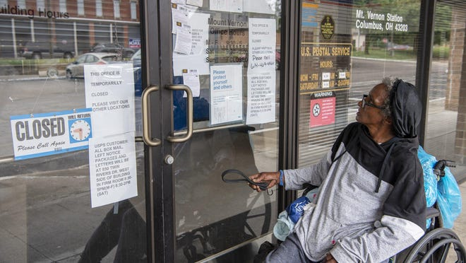 "Sannette Davis, who lives nearby on 21st Street, looks at signs on the closed doors of the post office at 327 N. 20th St. in Olde Towne East. ""There aren't any others in walking distance,"" Davis said. The Mt. Vernon branch of the U.S. Post Office on North 20th Street has been closed since June due to a broken air conditioning unit. Neighborhood residents are now having to travel to the Twin Rivers location in order to pick up packages and buy stamps."