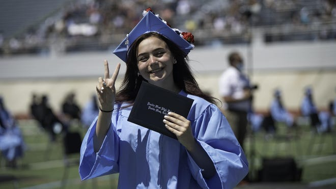 Pueblo West High School graduate Katelynn Henne throws up a peace sign Friday after receiving her diploma.