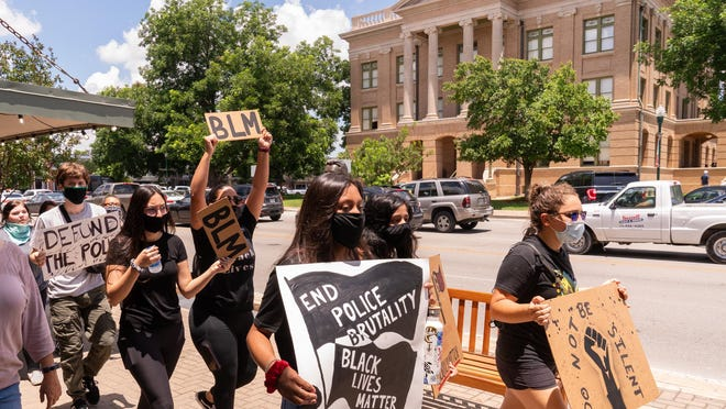 A group of protesters march around Georgetown Square on Wednesday decrying the death of George Floyd in Minnesota and police brutality against black Americans.