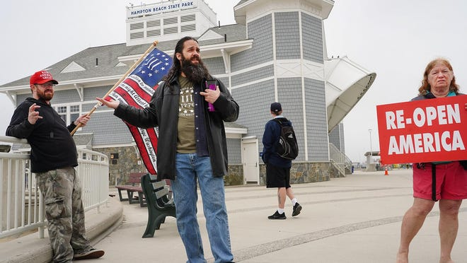"""Jeremy Cayford of Manchester, left, Frank """"Footloose"""" Staple, of Manchester and Cheryl Rounds of Derry, protest the closure of Hampton Beach on Memorial Day. ReopenNH plans a similar protest on June 6."""