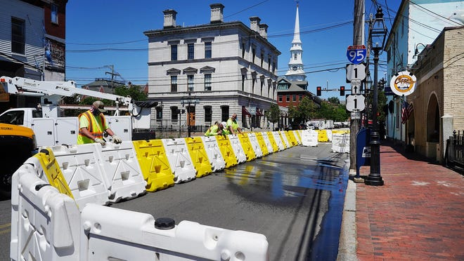 From left, Portsmouth Public Works employees Jim Carr, Jeff Boucher and Glenn Kelleher set-up barriers Tuesday to create outdoor dining for the Clipper Tavern on Pleasant Street.