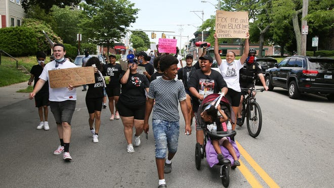 Demonstrators march down Broadway in Newport during a human rights rally Saturday.