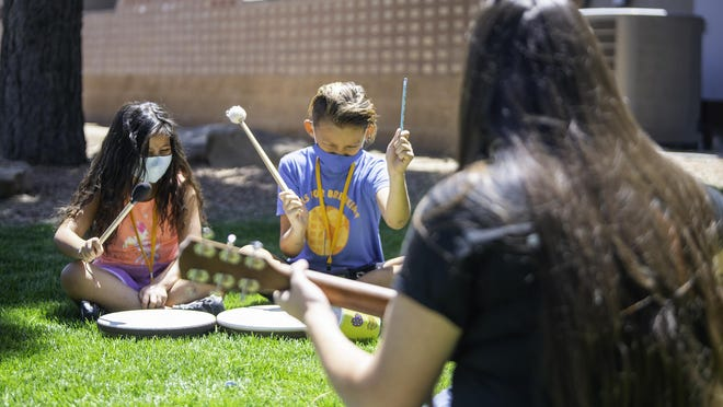 Chantel, left, and Damien bang drums as Becky Bressan plays the guitar during Sangre de Cristo Community Care's grief camp at the Steelworks Center of the West  Friday.