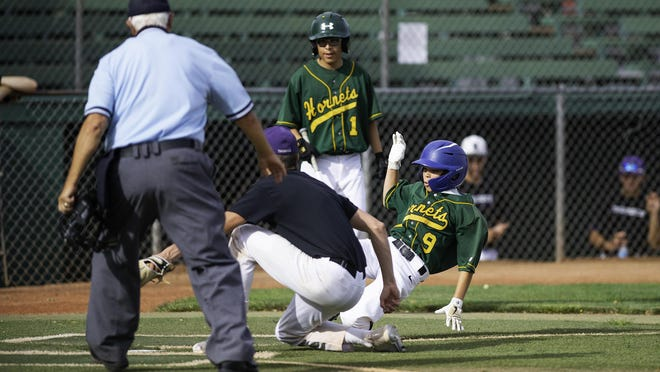 Pueblo County's Hunter Santisteven, right, slides into home plate for a run against Greenhorn Valley on Monday.