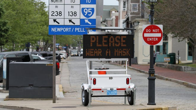 An electric sign Wednesday morning reminds visitors in downtown Newport to wear masks.