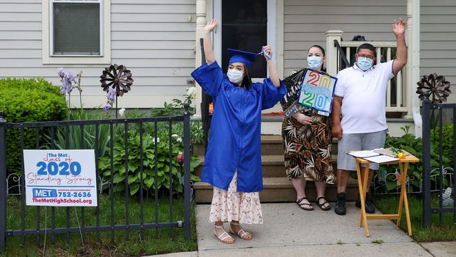 Shania Molina and her family wave after Met School leaders visited her house Friday morning to deliver her diploma.