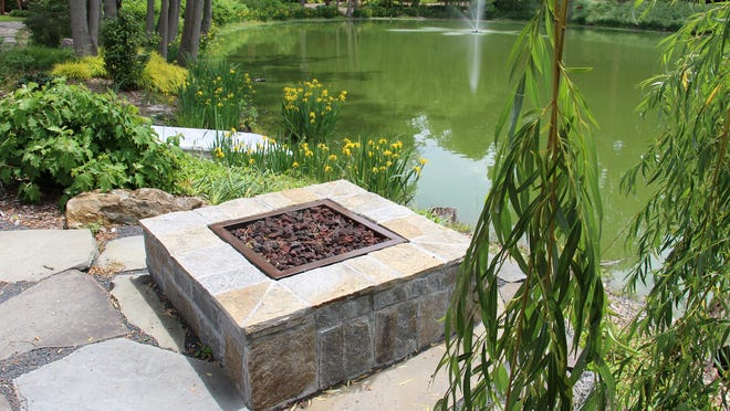 A firepit by a pond creates a tranquil remote work setting.