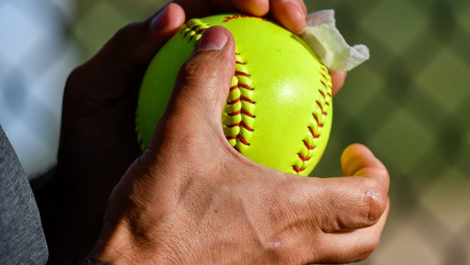 A softball is cleaned with a sanitizing wipe in between innings.