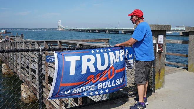 A man stand next to a Trump flag at the start of the boat rally in Newport on Sunday morning.