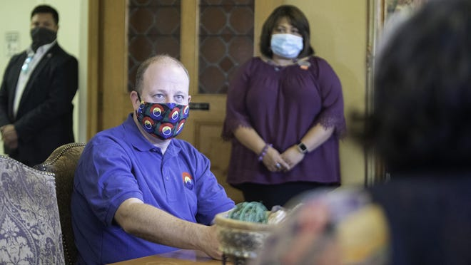 Gov. Jared Polis listens to board members of the YWCA of Pueblo during a whirlwind tour on Tuesday.