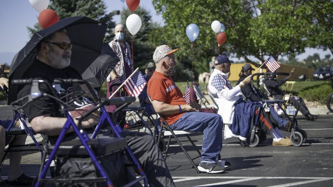 Veterans at the Pueblo VA Nursing Home watch as a cascade of floats and vehicles drive-by as part of the Home of the Hero Veteran Parade on Saturday.