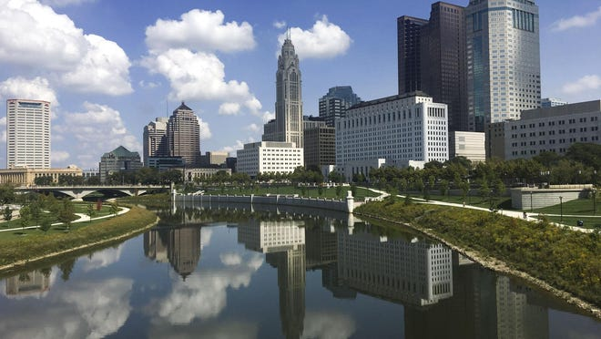 The downtown skyline is reflected in the Scioto River