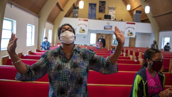Regina Hill, of Columbus, sings and claps along to hymns during Sunday morning service at Woodland Christian Church in Columbus, Ohio, on Sept. 13, 2020. With precautions in place, including temperature checks, mask requirements and hand sanitizing, a small group of worshipers attend services at Woodland Christian Church.