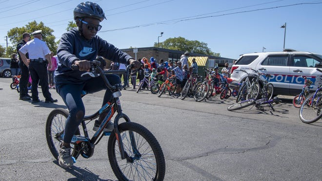 Hamadi Jama, 9, tries out his new ride after Columbus police and Starfish Assignment gave away about 75 refurbished bikes to kids at the Wedgewood Apartments complex on the Hilltop on Saturday.