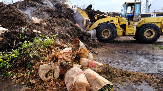 A front end loader removes leaves and yard waste from the Portsmouth Recycling Center. The Department of Public Works reminds residents that dumping fall leaves in or near water bodies and wetlands is against the law.