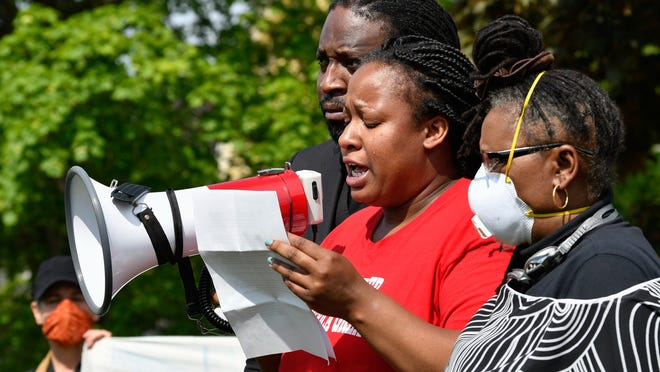 Caja Johnson addresses protestors outside the home of Gov. Charlie Baker in Swampscott as Rev. Andre Bennett, of Zion Baptist Church in Lynn, and Esther Ngotho, of Beverly Human Rights Committee, stand by her side during a Black Lives Matter rolling rally protest on Wednesday, June 3, 2020.