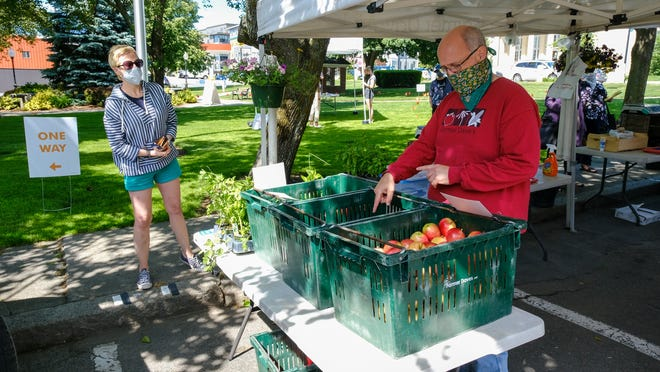 Lauren Barthold receives help from Jeff Todd with her purchase of apples at the Farmer Dave's booth on the first day of Beverly Farmers' Market on Monday, June 15.