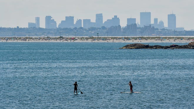 People surfing at Swampscott's King's Beach in August of 2020.
