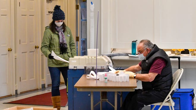 Poll worker Maura Feltault helps cast mail-in and early voter ballots along with Topsfield Constable Fred Capobianco inside the St. Rose Church polling location during the 2020 presidential election Tuesday, Nov. 3.
