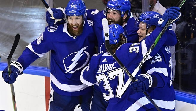 Tampa Bay Lightning left wing Ondrej Palat (18) celebrates after scores the winning goal on the Boston Bruins with teammates Braydon Coburn (55), Patrick Maroon (14) and Yanni Gourde (37) during overtime Tuesday.