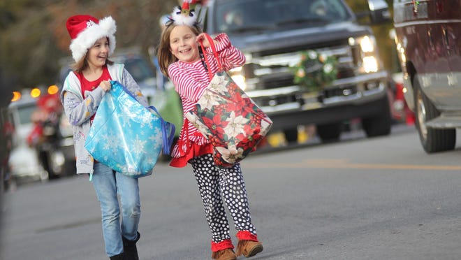 Children give candy away while walking in the Boiling Springs Christmas parade in 2018.