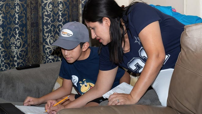 Jessica Molina, 39, helps her son, Juan, 10, with his math homework in their Pflugerville home. When school started this year, she was helping all four kids get onto their online classes while teaching her own preschool class and caring for her husband, Juan, who died a few days after school started of kidney cancer.