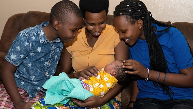 Esther Kinyana and her children Blessing, 8, and Gloria, 13, look on at baby Gladys, who arrived in early October. Kinyana and her husband, Albert Byishimo, were reunited in a refugee camp in Burundi after fleeing Congo. They arrived in Austin in 2019.