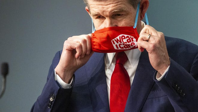 Gov. Roy Cooper removes his mask before speaking during a briefing on the state's coronavirus pandemic response Tuesday at the N.C. Emergency Operations Center in Raleigh.