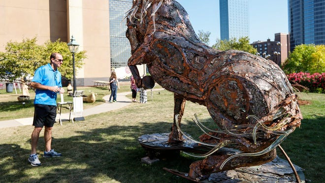 """Steve Dufon of Grand Haven, left, checks out sculpture """"Lux Maximus"""" made by Costa Mesa, CA artist Daniel Oropeza outside of the Grand Rapids Public Museum during ArtPrize Nine in Grand Rapids, September 22, 2017."""