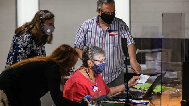 Poll workers gather around Rosemary Spatafora while wearing masks to assist her in spoiling an absentee ballot during the Michigan primaries at the community center in Pleasant Ridge, Mich. on Aug. 4, 2020.