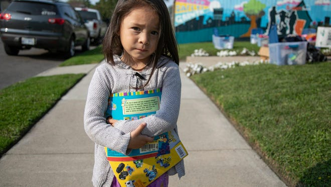 Miriam Villanueva, 4, hugs two books she just received Thursday, Sept. 24, 2020 at one of the houses that Brilliant Detroit operates near Southwest Detroit. Brilliant Detroit was doing its weekly supplies donations to families in need. Villanueva got a Dora the Explorer book and the popular Smash! Crash! by Jon Scieszka.