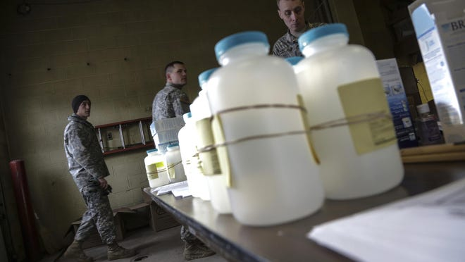 In this Jan. 18, 2016, file photo, water analysis test kits for Flint residents to pick up for lead testing in their drinking water are set out on a table at Flint Fire Department Station No. 1 as members of the U.S. Army National Guard 125th Infantry Battalion wait to help residents. Flint has taken important steps toward resolving the lead contamination crisis that made the impoverished Michigan city a symbol of the drinking water problems that plague many U.S. communities.