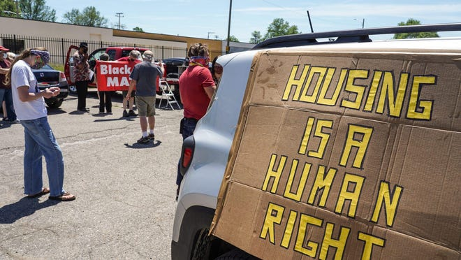 People gather at Butzel Family Center in Detroit's Islandview neighborhood with signs on their vehicles for the start of a caravan protest through Detroit neighborhoods while calling for relief for tenants and mortgage borrowers during Coronavirus pandemic on Tuesday, June 9, 2020. Detroit Eviction Defense called for the caravan in support of a new local tenant union and in anticipation of Governor Whitmer's executive order prohibiting evictions expiring at the end of this week.