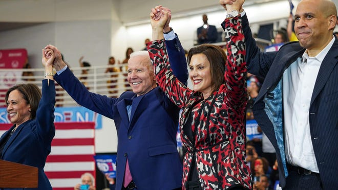From left to right, U.S. Sen. Kamala Harris of California, Democratic presidential candidate and former Vice President Joe Biden, Michigan Governor Gretchen Whitmer and U.S. Sen. Cory Booker raise arms after Biden takes the stage to speak to a crowd during a Get Out the Vote event at Renaissance High School in Detroit on Monday, March 9, 2020.