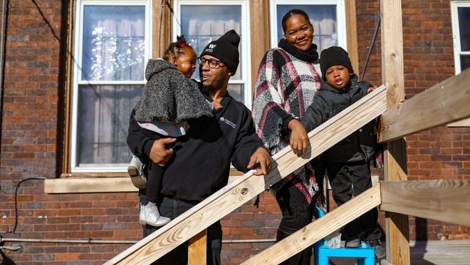 Kenzie E. Fuquay, 30, holds his daughter, Khloe, 2, on the back porch with his wife Shardaya Fuquay, 30, and their son Kenzie C. Fuquay, 3, in their backyard in Highland Park, Mich. on Nov. 18, 2020. Shardaya Fuquay, who is pregnant, is juggling the demands of being a stay-at-home parent and running a local nonprofit, Journey to Healing, that provides a holistic approach to trauma.