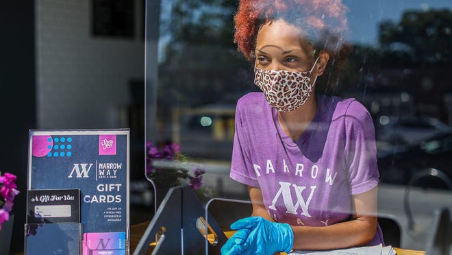 Barista Erika Hicks, 23, of Detroit serves coffee to Cheryl Spears, of Detroit at Narrow Way Cafe and Shop on the Livernois Avenue of Fashion in Detroit on July 17, 2020. Narrow Way recently reopened, but doesn't allow people to come inside, but serves customers through the bay garage door that now has a counter with plexiglass and all personnel wear masks.