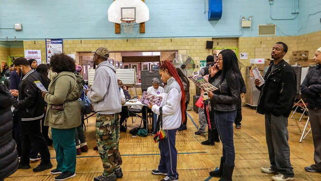 Voters stand in line waiting to cast their ballot at Bow Elementary school that has multiple precincts voting on Michigan midterm elections day in Detroit on Tuesday, Nov. 6, 2018.