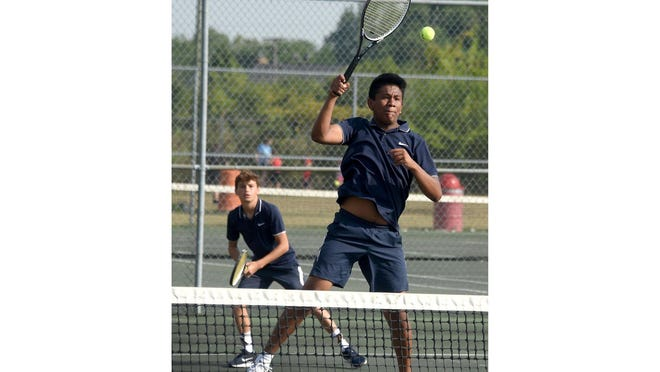 Carlos Mendoza of Airport strikes the ball at the net with his Jacob VanBuskirk in the background. Mendoza and VanBuskirk won at No. 1 doubles to help the Jets beat Monroe 7-1 Tuesday.