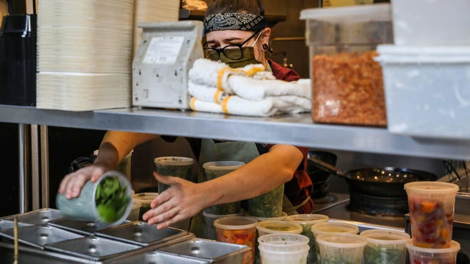 Line Cook Aubrey Vahosky preps her food station for upcoming delivery and carryout orders at Takoi restaurant in Detroit on Saturday, Nov. 21, 2020.