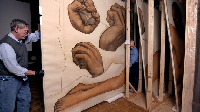 """Senior museum technician Michael Kociemba and Douglas Bulka, a paper care specialist at the DIA, move a mounted section of the Diego Rivera drawings into a specially built storage area. The drawings, made for the """"Detroit Industry"""" murals, will go on display with the upcoming exhibit """"Diego Rivera and Frida Kahlo in Detroit."""""""
