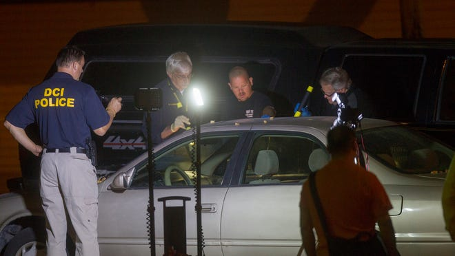 Crime scene investigators and police officers surround a Toyota Camry linked to the disappearance of 20-year-old Iowa State University student Tong Shao at an Iowa City apartment development late Friday. A body was found in the vehicle's trunk, but police had not announced its identity as of Saturday evening.