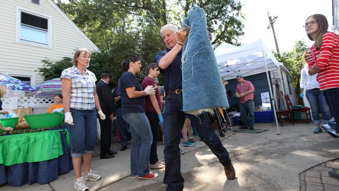 Governor Rick Snyder carries dripping wet carpeting on to the curb at the Cahaney home on Farnum Street in Royal Oak, Friday, Aug.15, 2014.